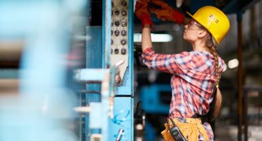 Female electrician or technician with screwdriver repairing machine at plant