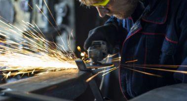 Factory worker using electric grinder in metal industry.