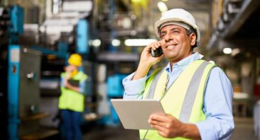 manufacturing manager holding a tablet talking on the phone